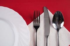 Placa de cena blanca vacía con la cuchara de sopa de plata de la bifurcación y del postre, aislada en fondo rojo del mantel con e Fotos de archivo