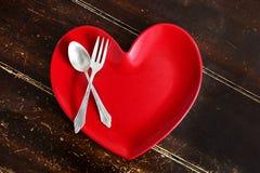 Placa de cena en forma de corazón con la bifurcación y cuchara en la tabla de madera gastada Foto de archivo libre de regalías