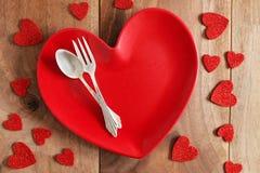 Placa de cena en forma de corazón con los cubiertos finos en la etiqueta de madera del tablón Fotos de archivo libres de regalías
