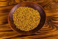 Placa de cerámica con polen de la abeja en la tabla de madera Foto de archivo