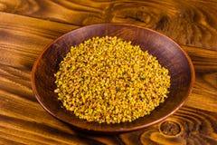 Placa de cerámica con polen de la abeja en la tabla de madera Foto de archivo libre de regalías