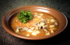 Placa de cerámica de la sopa de verduras que se coloca en harpillera teñido Foto de archivo
