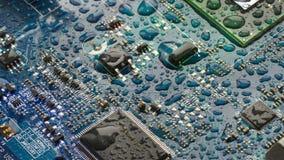 A placa de circuito do cartão-matriz é coberta com as gotas da água em tons azul esverdeado foto de stock
