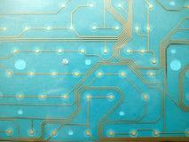 Placa de circuito hecha del plástico con los rastros de circuito en fondo azul El concepto de tecnología, computando, electrónica imagenes de archivo