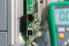 Placa de circuito impresa electrónica de la impresora laser con los conectores USB y RJ45 y el multímetro Foto de archivo libre de regalías