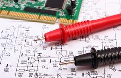 Placa de circuito impresso e cabo do multímetro no diagrama da eletrônica Imagens de Stock
