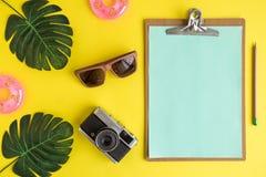 Placa de clipe de papel vazia com óculos de sol, câmera da foto, o flutuador inflável e o sumário do verão das folhas do monstera fotos de stock