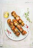 Placa de corte branca com os espetos saborosos da carne no fundo rústico claro Fotos de Stock