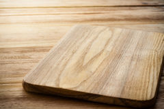Placa de corte brilhante em uma tabela de madeira Imagens de Stock