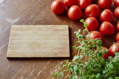 Placa de corte cercada por ervas e por tomates Imagens de Stock