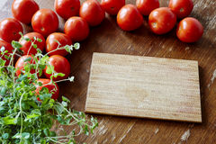 Placa de corte cercada por tomates imagens de stock