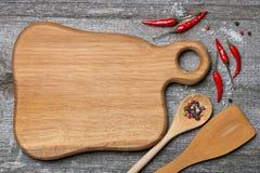Placa de corte, colher, espátula e especiarias de madeira figuradas, vista superior Fotografia de Stock