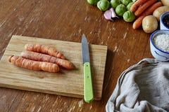 Placa de corte com as três cenouras cruas fotos de stock