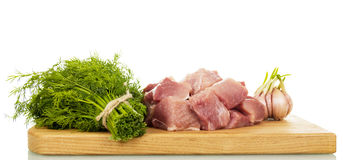 A placa de corte com carne de porco crua cortou o aneto e o alho isolados Foto de Stock Royalty Free