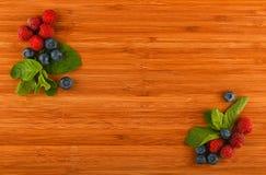Placa de corte com mirtilos, framboesas e folhas de hortelã em c imagem de stock
