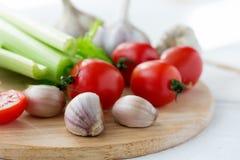 Placa de corte com os legumes frescos na tabela de madeira branca Imagens de Stock Royalty Free