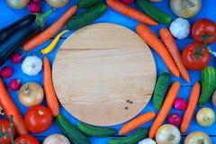Placa de corte com pimenta preta unpowdered entre legumes frescos Imagem de Stock