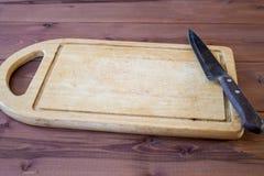 Placa de corte com uma faca de cozinha em atable Imagens de Stock Royalty Free