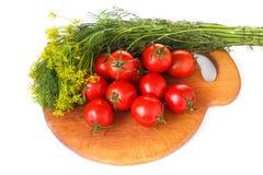 Placa de corte com verdes aneto e tomate no fundo branco Imagens de Stock Royalty Free