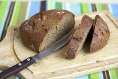 Placa de corte de madeira com pão fotografia de stock royalty free