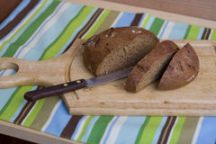 Placa de corte de madeira com pão cortado fotos de stock