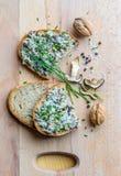 Placa de corte de madeira com pão, propagação, cebolinha Foto de Stock