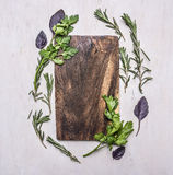 Placa de corte do vintage com as ervas no lugar rústico de madeira do fim da opinião superior do fundo para o texto, quadro Foto de Stock