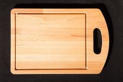 Placa de corte em um fundo escuro Fotografia de Stock