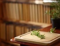 Placa de corte de madeira com alecrins próximo, livros no fundo, interior acolhedor da casa Imagens de Stock Royalty Free