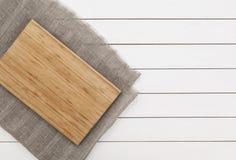 Placa de corte na tabela de madeira branca Fotografia de Stock Royalty Free