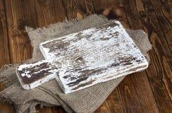 Placa de corte velha com o pano de serapilheira na tabela de madeira Imagens de Stock