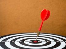 Placa de dardo com a seta dos dardos no centro do alvo Imagem de Stock