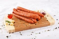 Placa de desbastamento de madeira com salsichas e especiarias Fotos de Stock Royalty Free