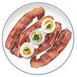 Placa de Fried Bacon Rashers con las rebanadas del huevo duro aisladas Imagen de archivo