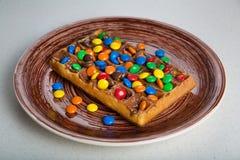 Placa de galletas belgas con el caramelo coloreado Imágenes de archivo libres de regalías