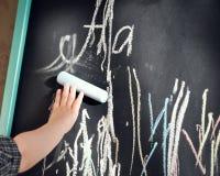 A placa de giz preta rabiscou o rapaz pequeno coloriu pastéis Aprendendo o alfabeto e preparação para a escola foto de stock