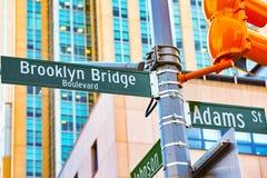 Placa de identificação do sinal de rua da ponte de Brooklyn e da rua de Adams e fotografia de stock