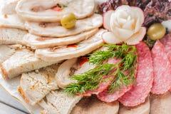 Placa de la carne con los pedazos deliciosos de jamón cortado, de salchicha, de aceitunas, de lengua de carne de vaca, de hierbas Fotos de archivo