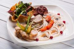 Placa de la carne con los pedazos deliciosos de jamón, de tomates de cereza, de hierbas y de carne cortados con el arándano Ciérr Imágenes de archivo libres de regalías