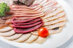 Placa de la carne con los pedazos deliciosos de jamón, de tomates de cereza y de carne cortados Ciérrese para arriba con el foco  Foto de archivo