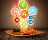 Placa de la comida con la comida deliciosa y símbolos sanos de la vitamina Imagen de archivo libre de regalías
