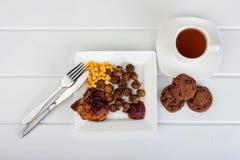 Placa de la comida y de una taza de té en un fondo de madera blanco fotos de archivo libres de regalías