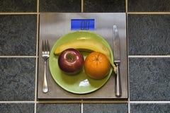 Placa de la fruta en una escala del peso Imagenes de archivo
