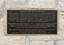 Placa de la información para un par de esculturas del águila calva que flanquean la entrada a Memorial Park del veterano, Ennis,  imagen de archivo libre de regalías