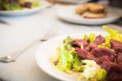 placa de la molleja con la ensalada y el pan casero Foto de archivo