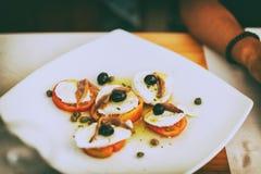 Placa de la mozzarella con el tomate en el restaurante fotos de archivo
