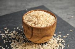 Placa de la pizarra con arroz sin pulir crudo en cuenco fotos de archivo libres de regalías