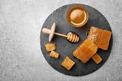 Placa de la pizarra con los panales y la miel deliciosa Fotos de archivo