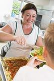 Placa de la porción de Lunchlady del almuerzo en una escuela Imágenes de archivo libres de regalías