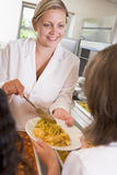 Placa de la porción de Lunchlady del almuerzo en una escuela Imagen de archivo